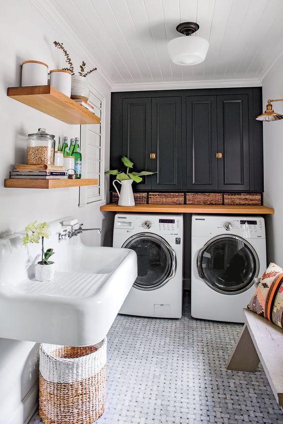 laundry room, patterned floor, white wall, black cabinet, wooden table, white sink, wooden shelves, wooden bench, rattan basket,