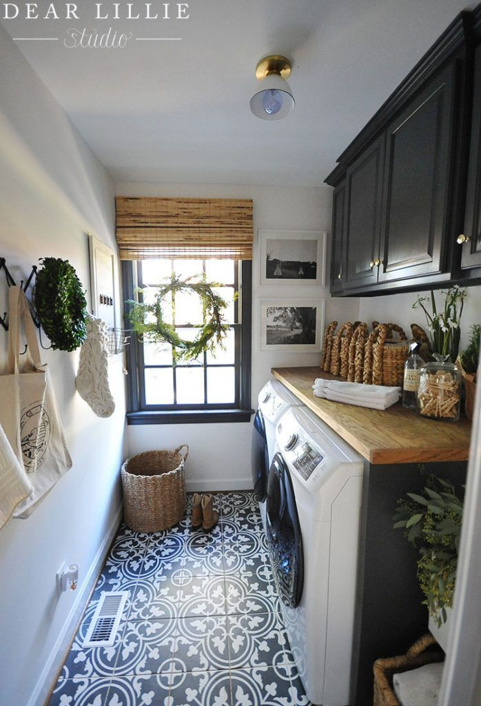 laundry room, white wall, patterned floor tiles, black cabinet, wooden counter top, black framed window