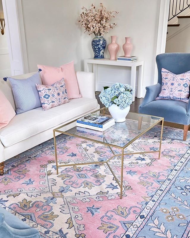 living room, pink blue patterned rug, blue chairs, white sofa, pink blue pillows, golden framed glass coffee table, white console table