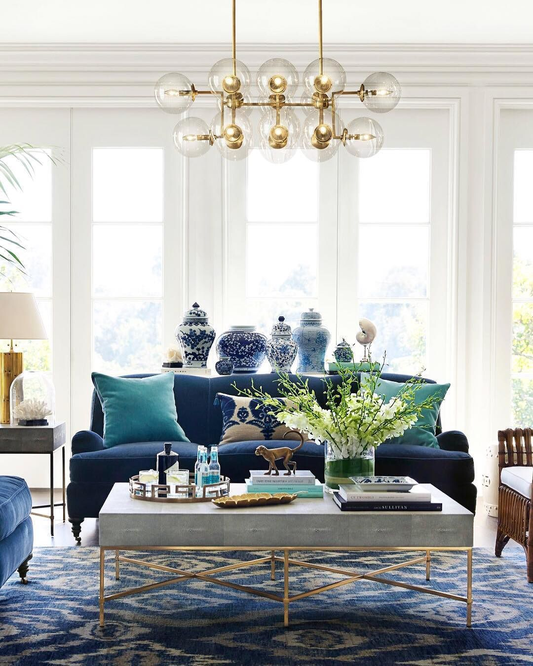 living room, white floor, blue patterned rug, blue sofa, grey coffee table with golden lines, blue white chinas, modern chandelier
