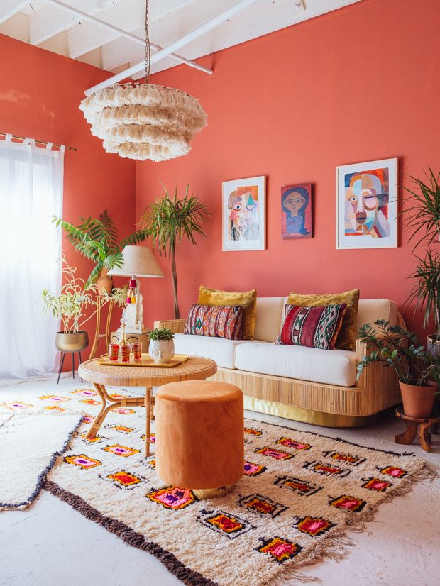 living room, white floor, patterned rug, orange wall, brown sofa, white cushion, round wooden coffee table, brown ottoman, fringe pendant