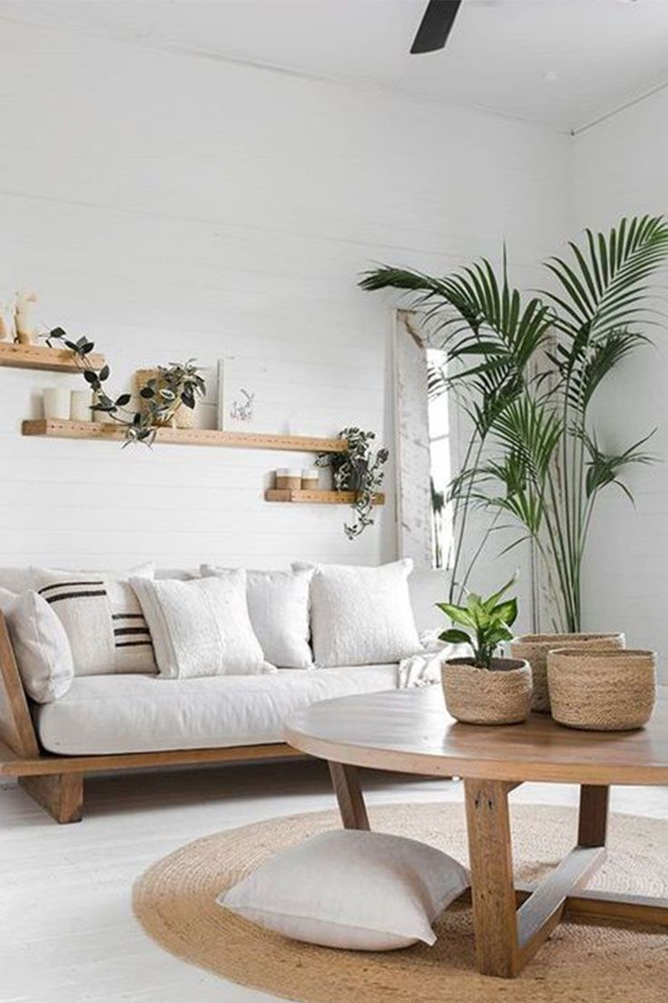 living room, white floor, rattan round rug, wooden round coffee table, white wall, wooden sofa with white cushion, floating shelves