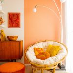 Living Room, White Orange Wall, Orange Round Ottoman, Rattan Chair, White Cushion, Wooden Cabinet, White Floor Lamp