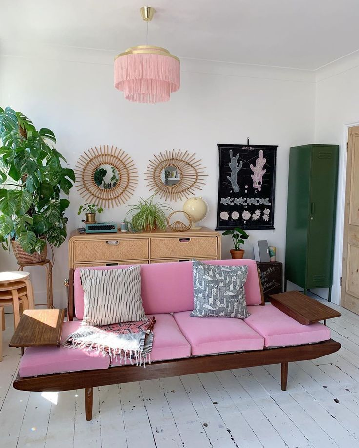 living room, white wooden floor, white wall, rattan cabinet, wooden bench, pink cushion, pink fringe chandelier, plants, green cabinet