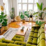 Living Room, Wooden Floor, Green Tufted Cornered Sofa, Green Tufted Ottoman, Plants All Over The Room, Rattan Round Chair, White Rug, Wooden Rectangular Coffee Table