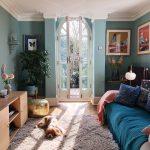 Living Room, Wooden Floor, Light Teal Wall, Dark Green Sofa, Rug, Plants, Wooden Cabinet
