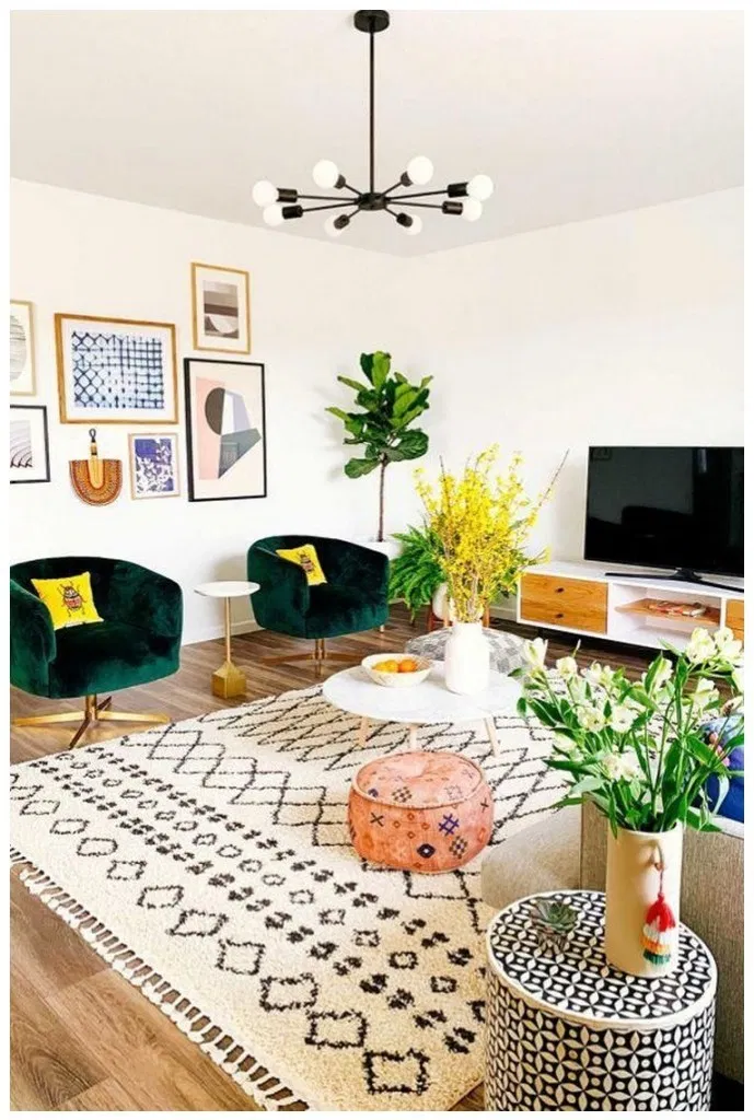 living room, wooden floor, patterned rug, green velvet chairs, white round coffee table, white cabinet, grey chairs, orange ottoman