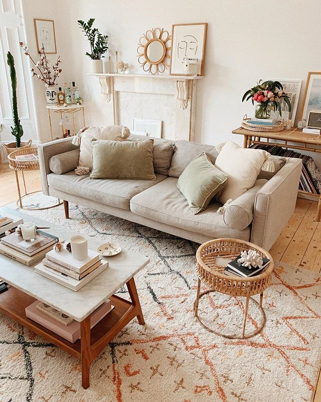 living room, wooden floor, white rug, grey sofa, white marble coffee table, white wall, marble fireplace, rattan side table