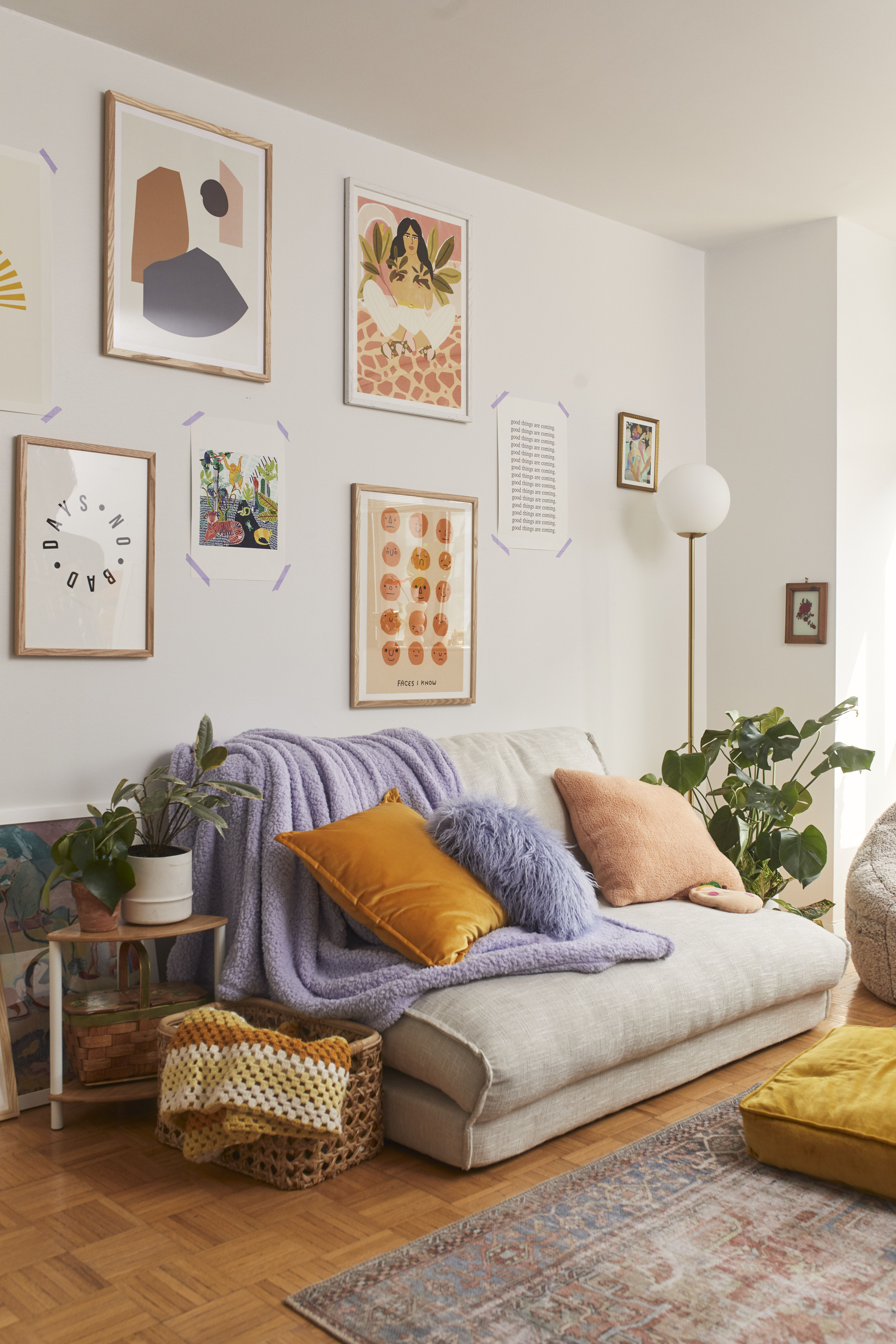 living room, wooden floor, white wall, grey foldable sofa, yellow ottoman, side table, white bulb floor lamp