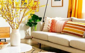 living room, wooden floor, white wall, white sofa, white coffee table, white patterned rug, orange ottoman, yellow curtain, wooden cabinet