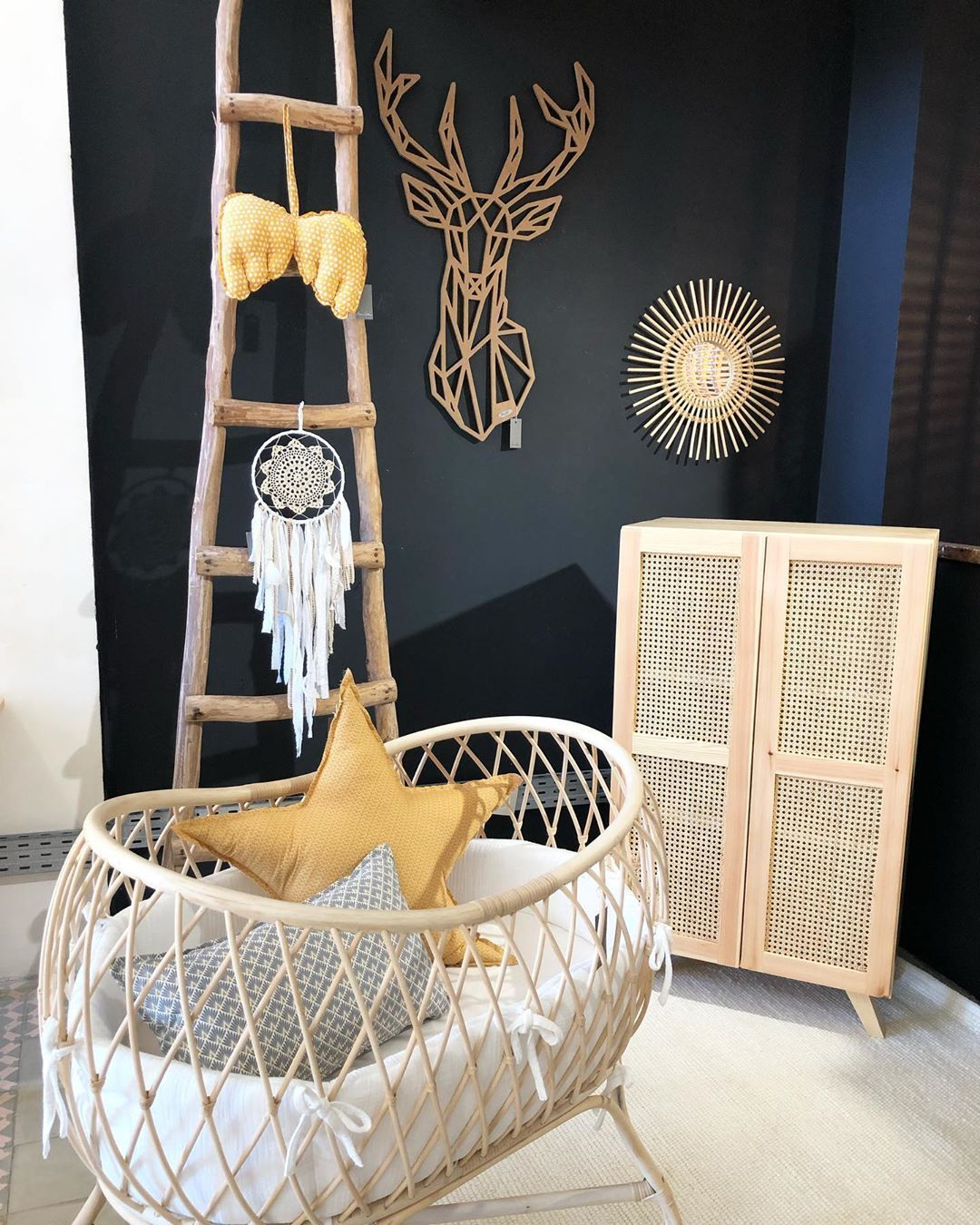 nursery, white floor, black wall, rattan crib, wooden rack, wooden rattan cupboard