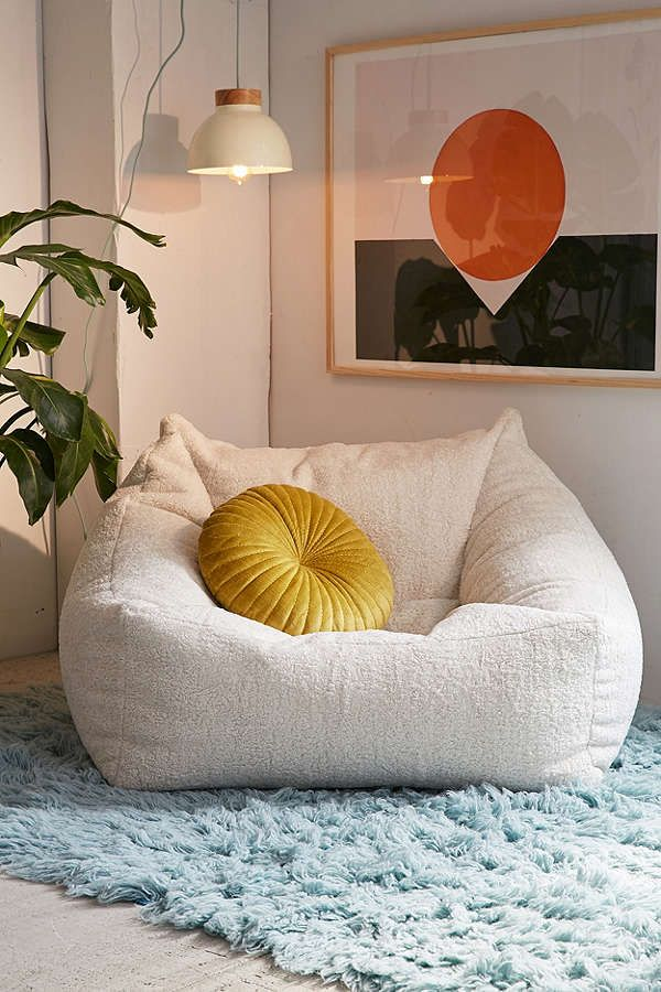 off white bean bag, grey floor, blue rug, white wall, yellow pillos