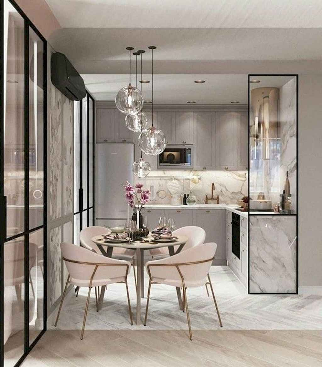 open kitchen, white marble floor, grey cabinet, glass pendants, grey marble backsplash, round table, soft pink chairs, golden legs, glass partition