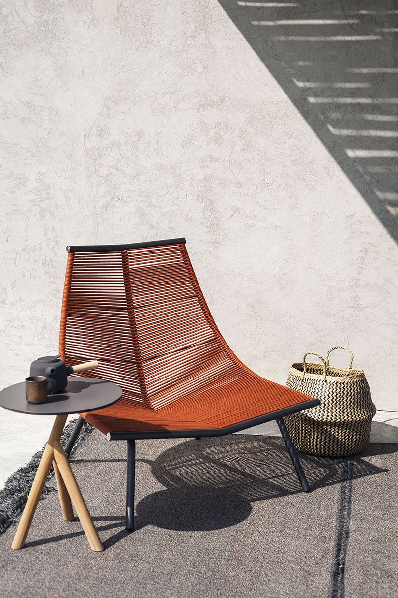 orange woven chair, black small round arble, rug, rattan basket