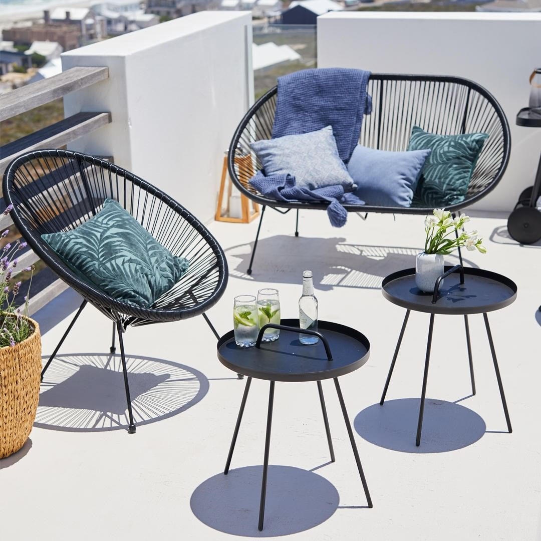 patio, white seamless floor and wall, black rattan sofa and chair, black tray chairs