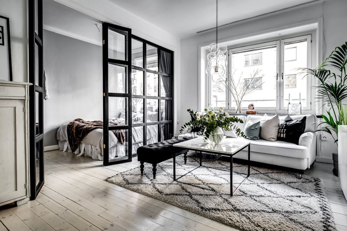 small apartment, wooden floor, grey wall, white sofa, black tufted bench, black white coffee table, glass pendants, rug