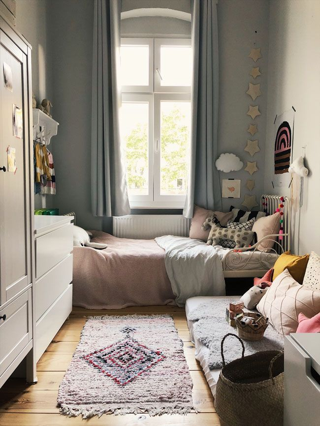 small bedroom, wooden floor, light sage green, white metal bed platform, pink blanket, white cabinet, white cupboard