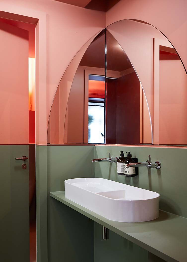 white sink, orange wall, green wall, half round mirror