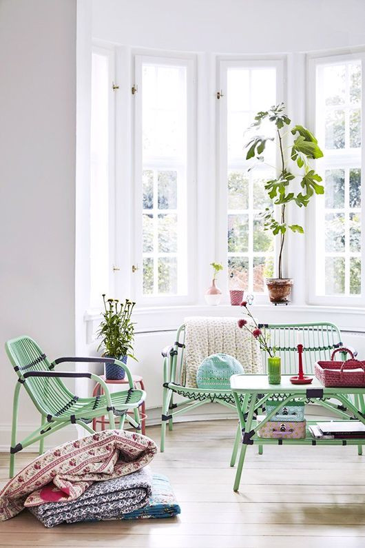 white wall, wooden floor, green rattan sofa and chairs, green rattan coffee table,