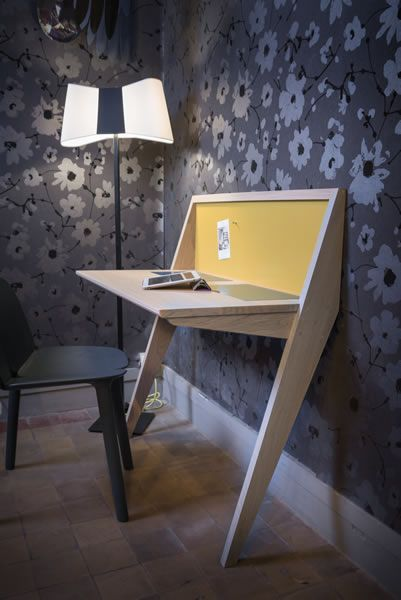 wooden table, angled legs, black chair, yellow board, floor lamp, flower wallpaper