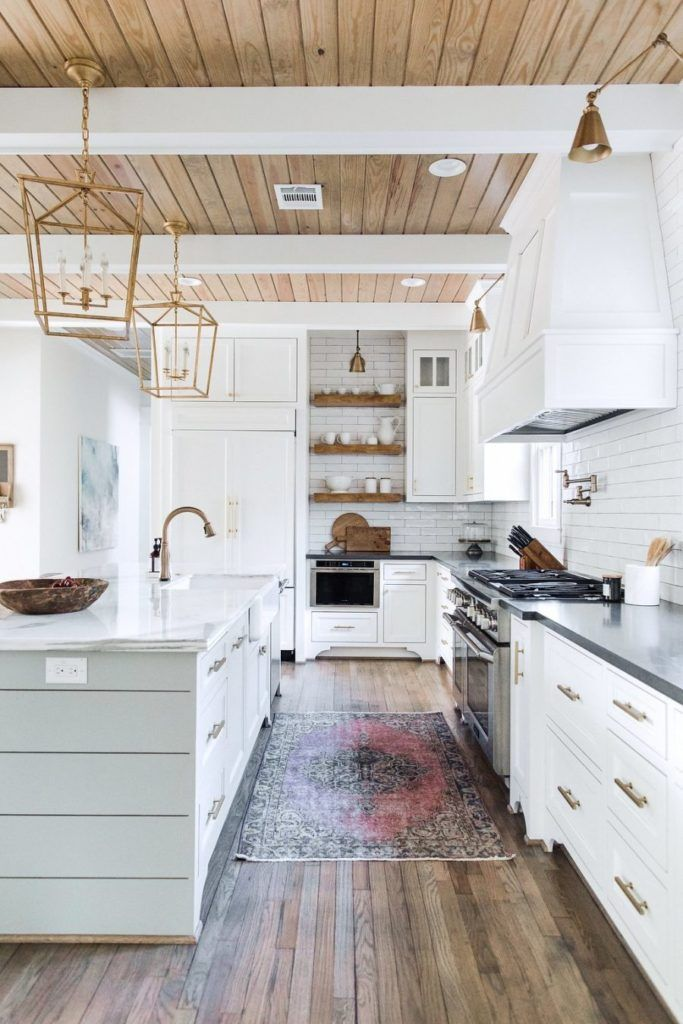accent ceiling, wooden boards on ceiling, white beams, golden iron chandelier, white cabinet, white subway wall tiles, wooden floating shelves