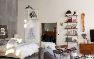 apartment, seamless grey floor, concrete wall, white wall, white bed, grey sofa, pink patterned rug, coffee table, floating shelves, wooden Tv cabinet