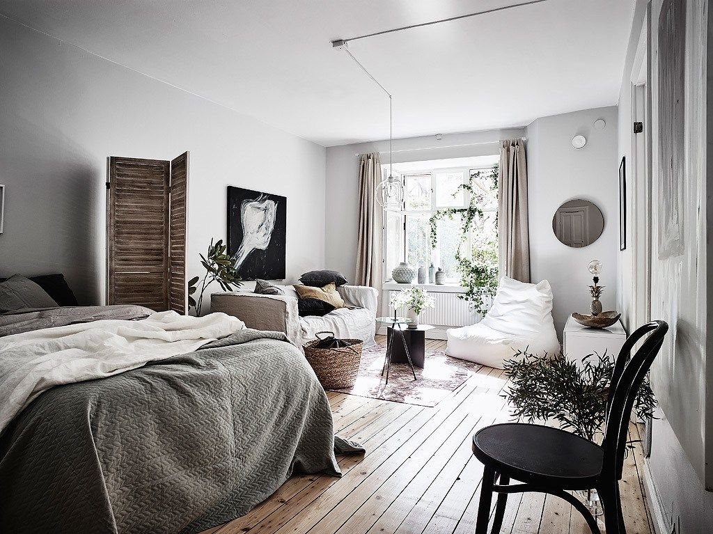 apartment, wooden floor, white wall, white bean bag, white sofa, coffee table, bed, wooden screen, black coffee table
