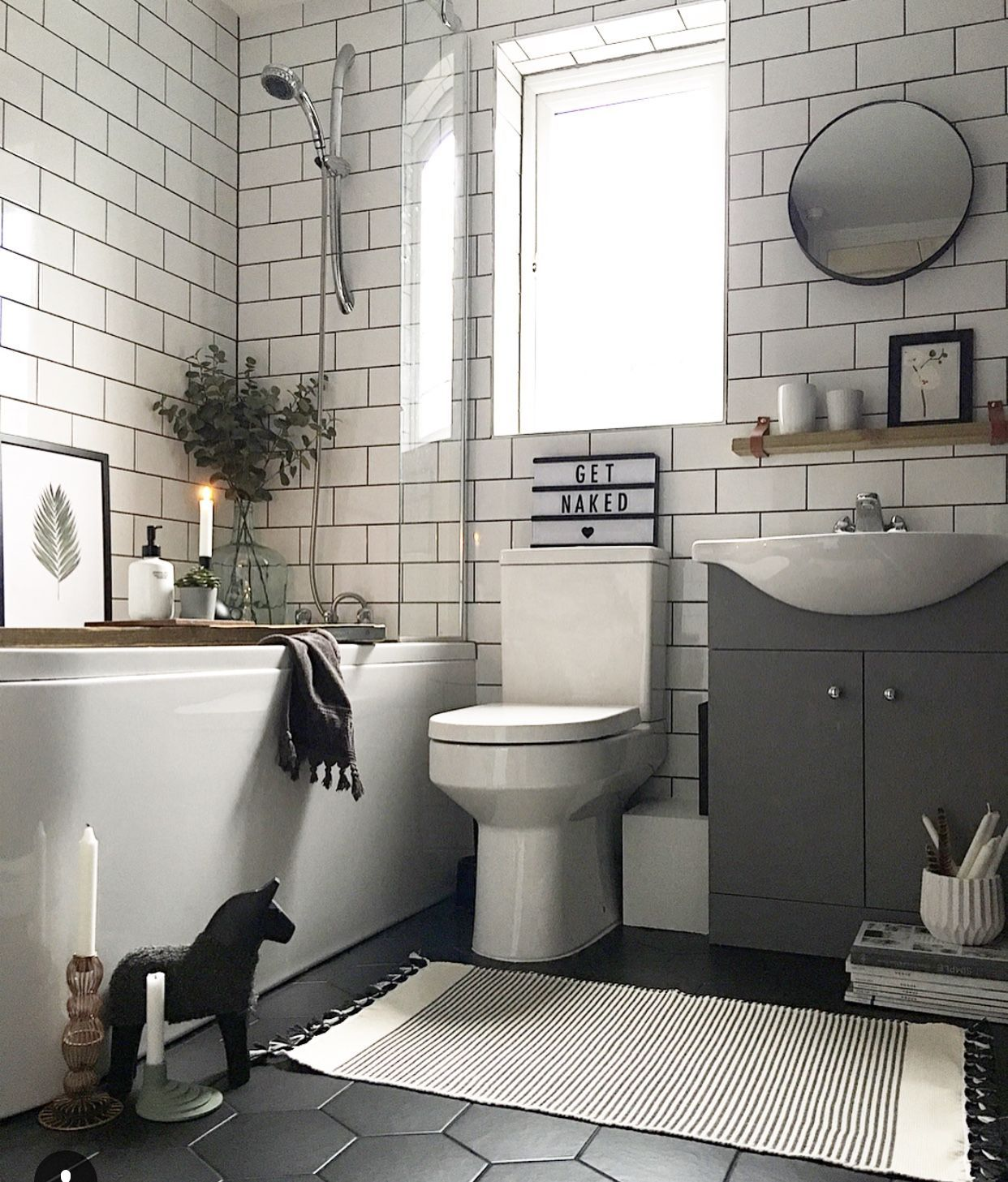 bathroom, black floor, white subway wall, white tub, grey cabinet with white sink, white toilet, round mirror