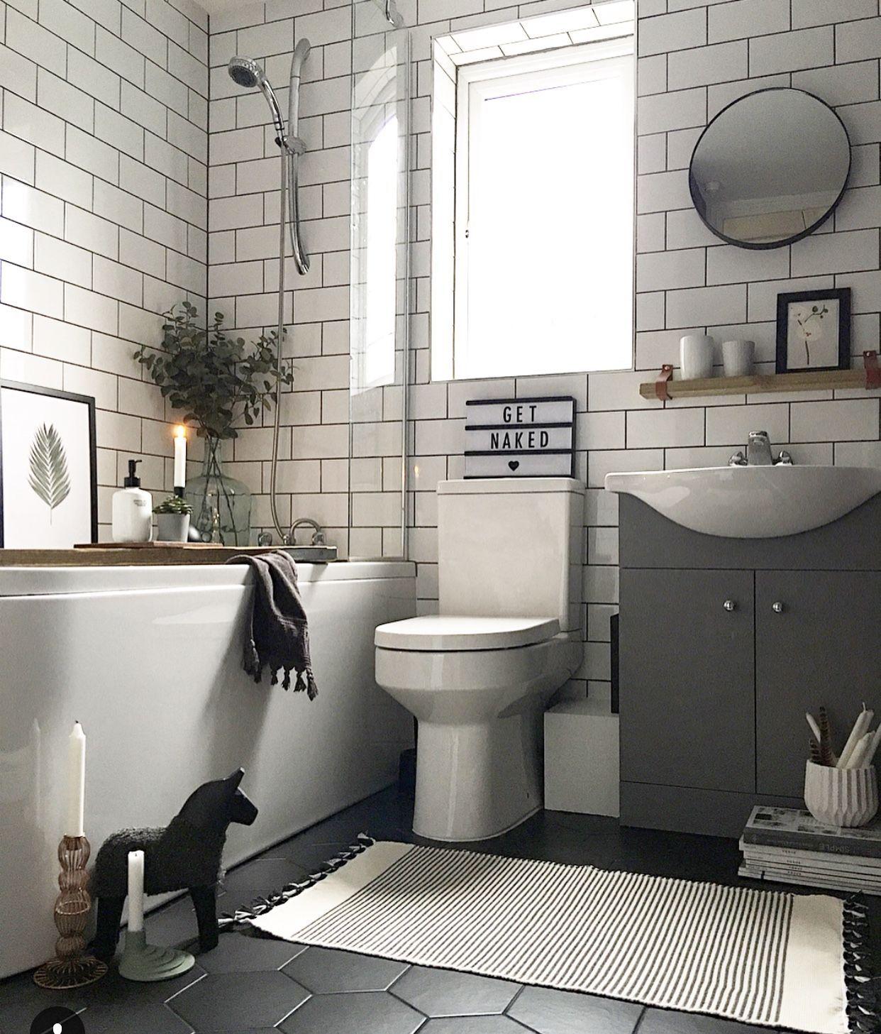 bathroom, black floor, white subway wall, white tub, grey cabinet with white sink, white toilet, round mirror