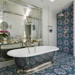 Bathroom, Blue Green Patterned Tiles On The Wall And Floor, White Subway Tiles, Silver Tub, Mirror