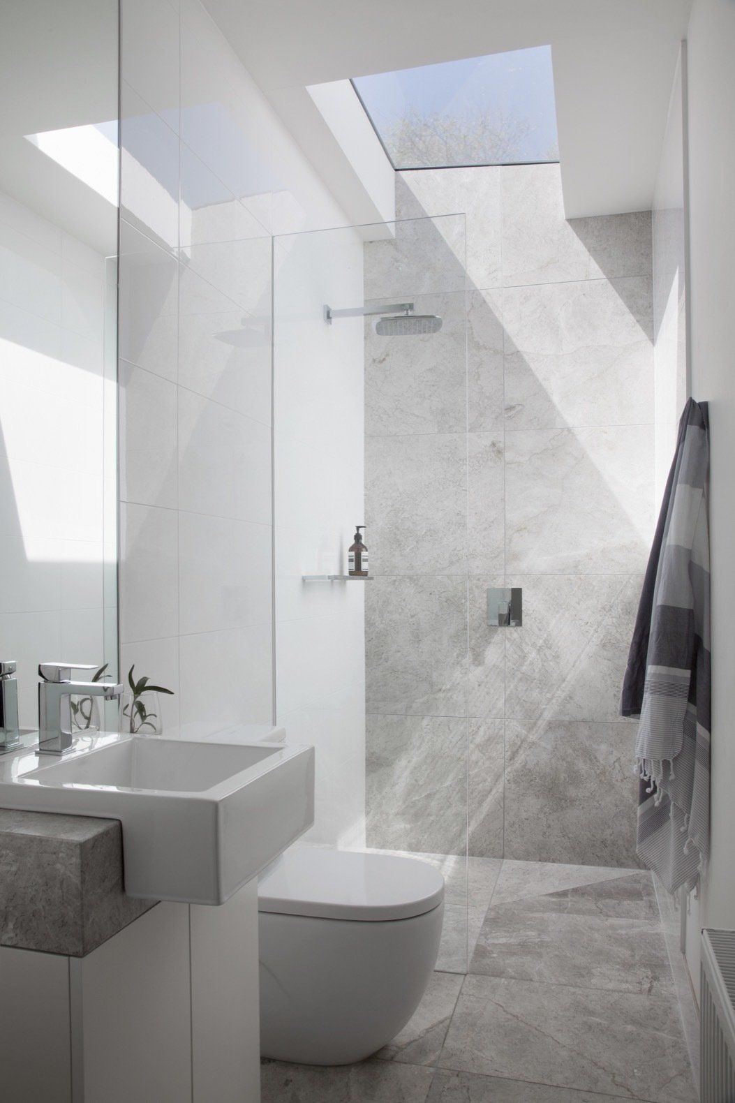 bathroom, grey marble floor, grey marble wall, white toilet, white floating sink, glass partition, glass ceiling