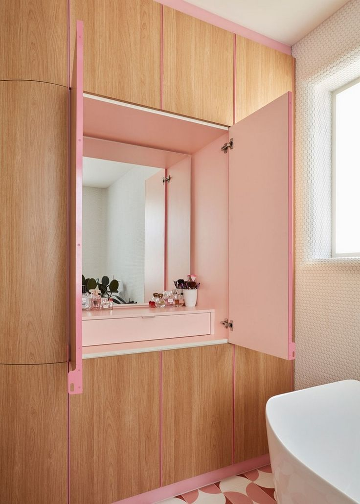 bathroom, pink patterned floor tiles, wooden cabinet with pink space inside with drawers, white tiny wall tiles white tub