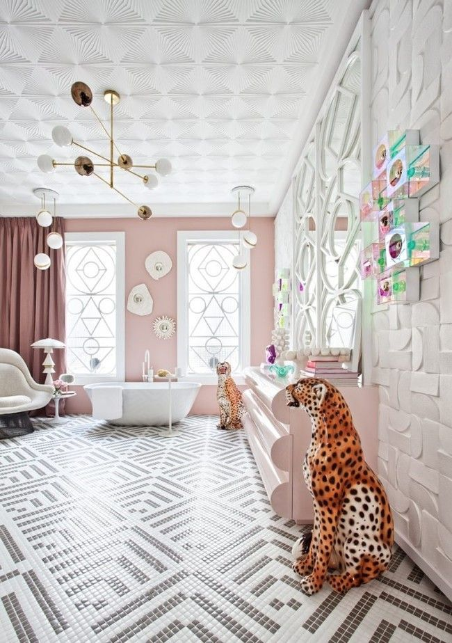 bathroom, pink wall, accent wall, pink cabinet, white tub, white pendants, white chairs, tiny floor tiles, framed mirror