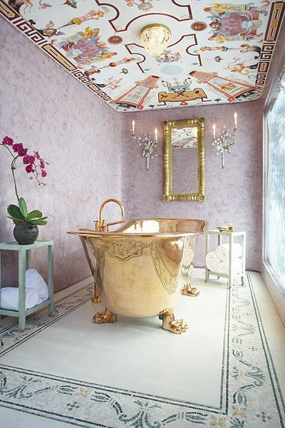 bathroom, pink wall, colorful patterned ceiling, golden framed mirror, golden tub, white patterned rug, sconces
