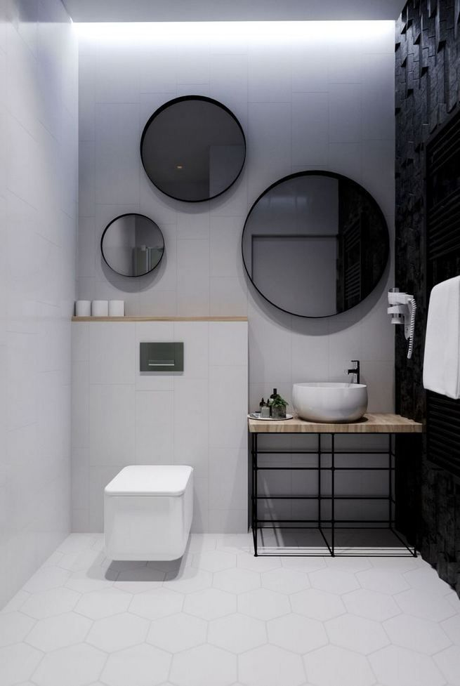 bathroom, white hexagonal floor tiles, black wall, white wall, whtie toilet, round mirror, vanity table, white round sink