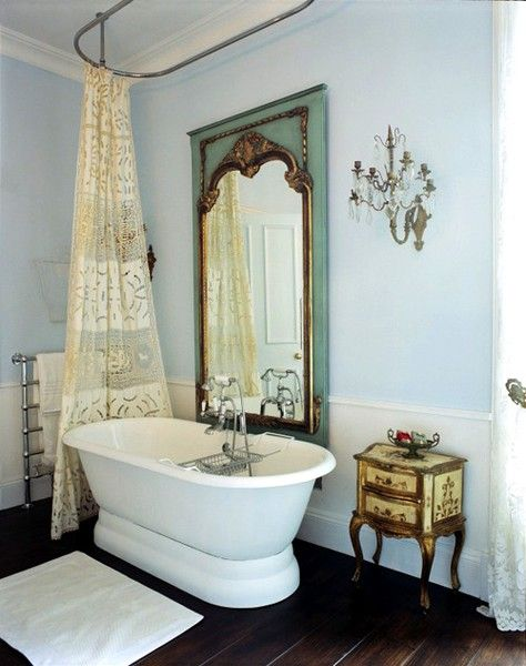 bathroom, wooden floor, white wainscoting, blue wall, green golden framed mirror