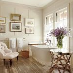 Bathroom, Wooden Floor, White Wainscoting, White Tub, Golden Side Table, White Tufted Chair, White Shade On The Window, Paintings, Rattan Basket