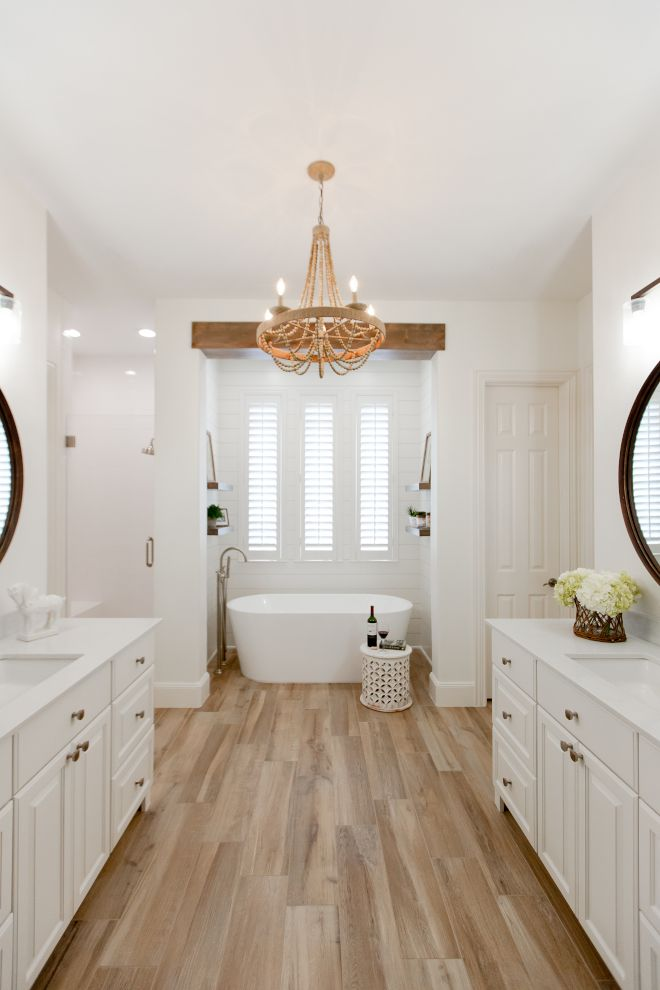 bathroom, wooden floor, white wall, chandelier, white cabinet, white tub, windows