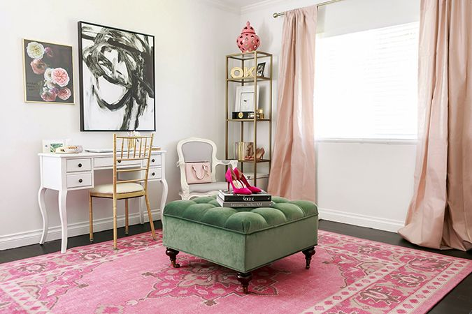 beauty room, black floor, pink patterned rug, green tufted ottoman, white wall, white table, golden chair, white chair, shelves