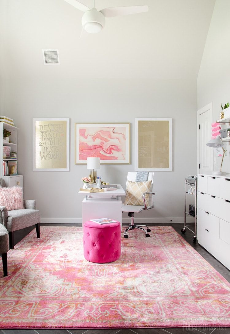 beauty room, dark wooden floor, white wall, pink patterned rug, pink tufted ottoman, grey chair, white table, white chair, white cabinet, white shelves