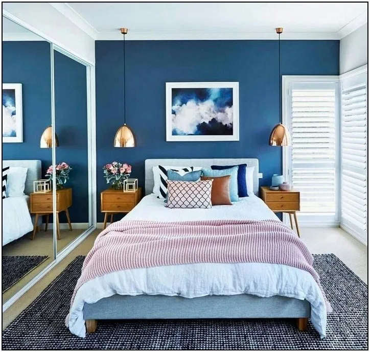 bedroom, brown floor, grey rug, gold pendants, wooden side cabinet, grey headboard, blue accent wall, white wooden screened window