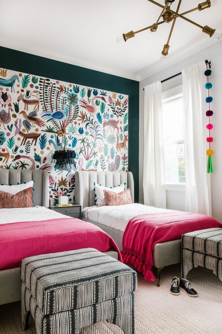 bedroom, brown floor, patterned accent wall, grey bed platform, ottoman, pink blanket, grey side cabinet