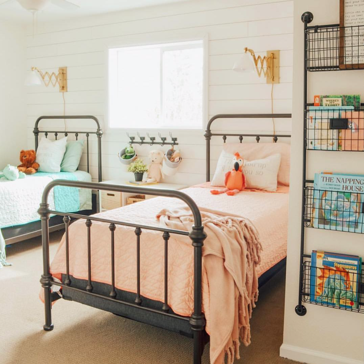 bedroom, brown floor, white woodplanks, black iron bed platform, orange bedding, blue bedding, sconces, black iron sheles