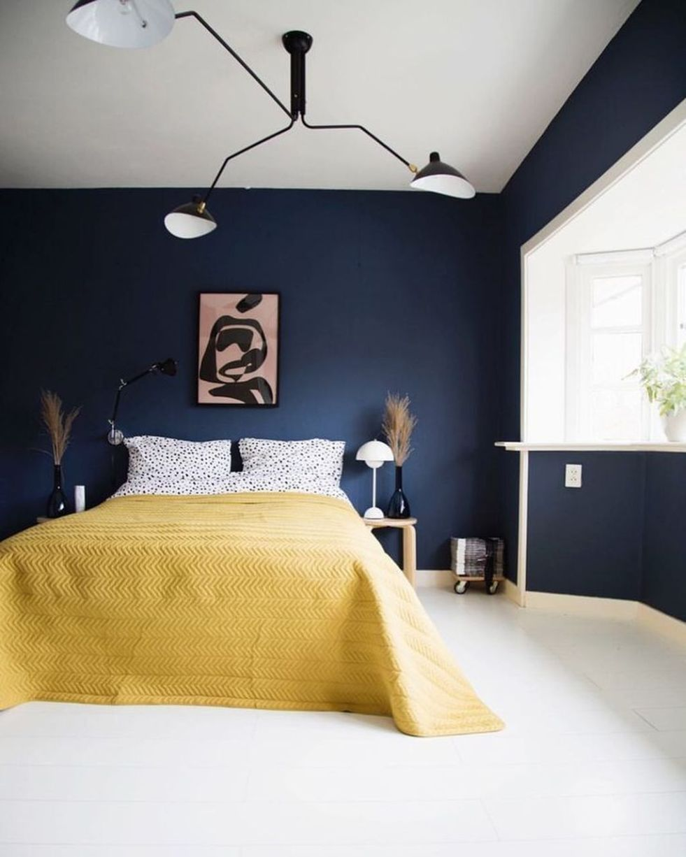 bedroom, white floor, dark blue wall, modern pendant, window, yellow bedding, wooden side table