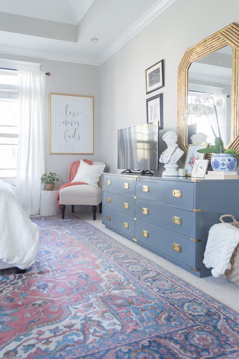 bedroom, white floor, patterned rug, white wall, golden framed mirror, blue cabinet with golden accents, white corner chair