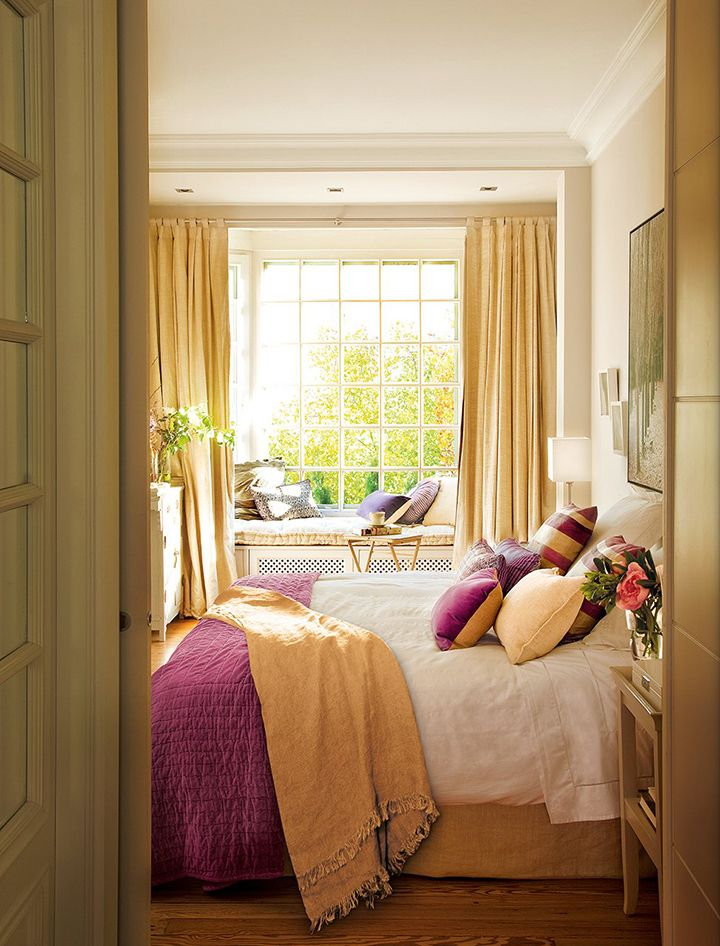 bedroom, wooden floor, bed, window seat with cushion, yellow curtain, white table lamp