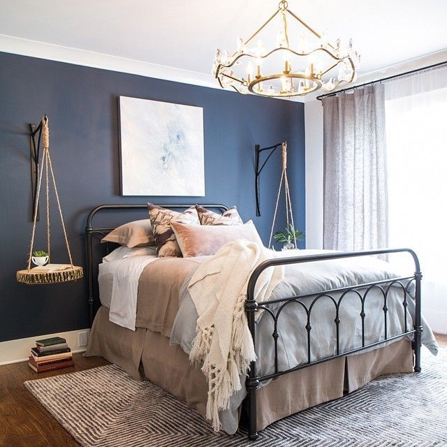 bedroom, wooden floor, rug, iron bed frame, floating side table, dark blue accent wall, modern chandelier