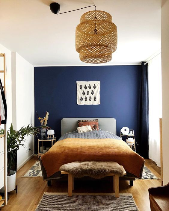 bedroom, wooden floor, white wall, blue accent wall, rattan pendant, grey headboard, wooden bench