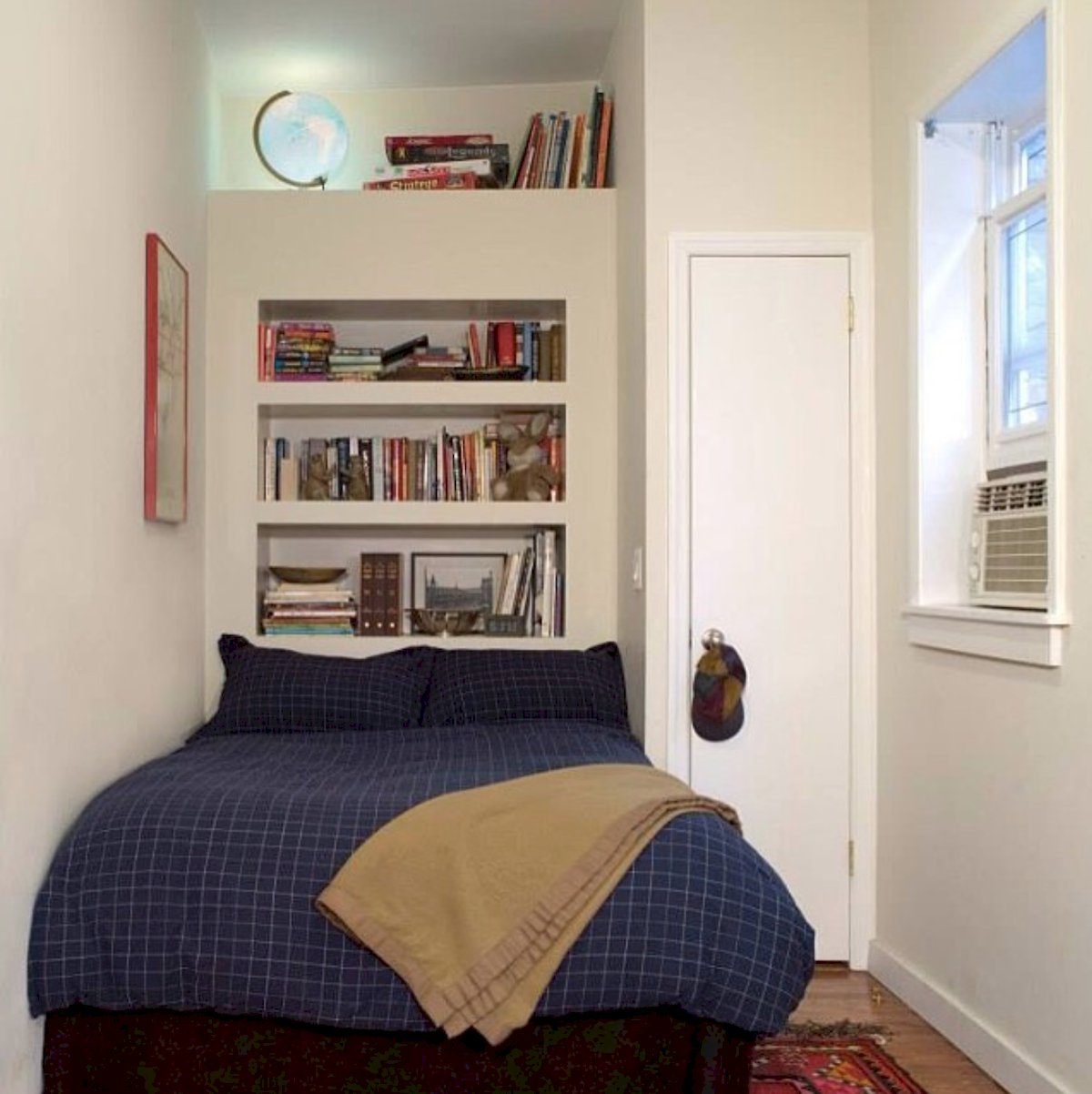 bedroom, wooden floor, white wall, indented shelves, dark blue bedding, glass window