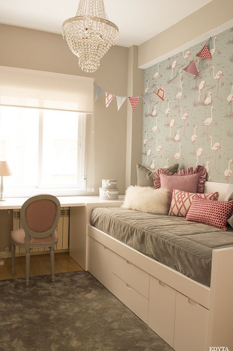 bedroom, wooden floor, white wall, wallpaper, white bed platform with drawers, grey bedding, white table, pink chair, pink pillows, chandelier